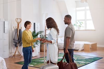 Female host handing keys to a young couple in a bedroom.