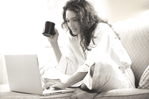 A woman in a robe working on a laptop