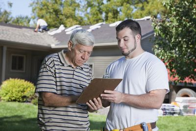 Man signing a guaranteed maximum price contract with contractor.