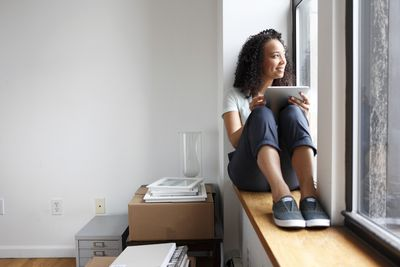 Woman near window with digital tablet in enjoying window view from new apartment.