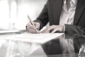 man signing an LLC partnership agreement