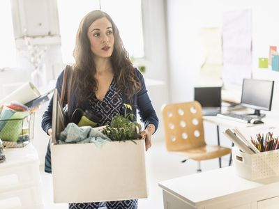 A woman who was just laid off leaving an office carrying a box with personal items.
