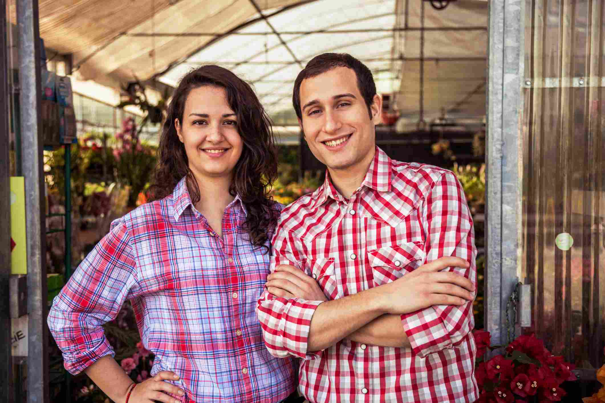 Couple standing in front of their gardening greenhouse