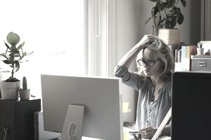 Stressed woman holding credit card at computer in home office