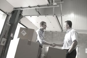 A supplier shaking hands with an ethical buyer by a loading dock door.