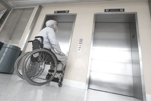 A man in a wheelchair waits for an elevator.