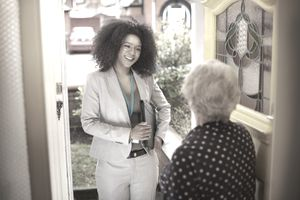 Door-to-door market researcher asking an older woman survey questions.
