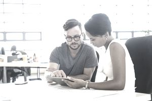 Man and woman in office using tablet