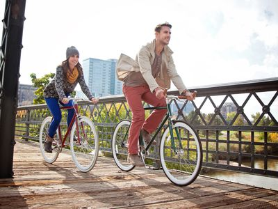Two young renters in Colorado riding their bikes across a bridge in Denver.