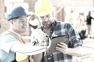 Construction foremen reviewing plans on a digital tablet.
