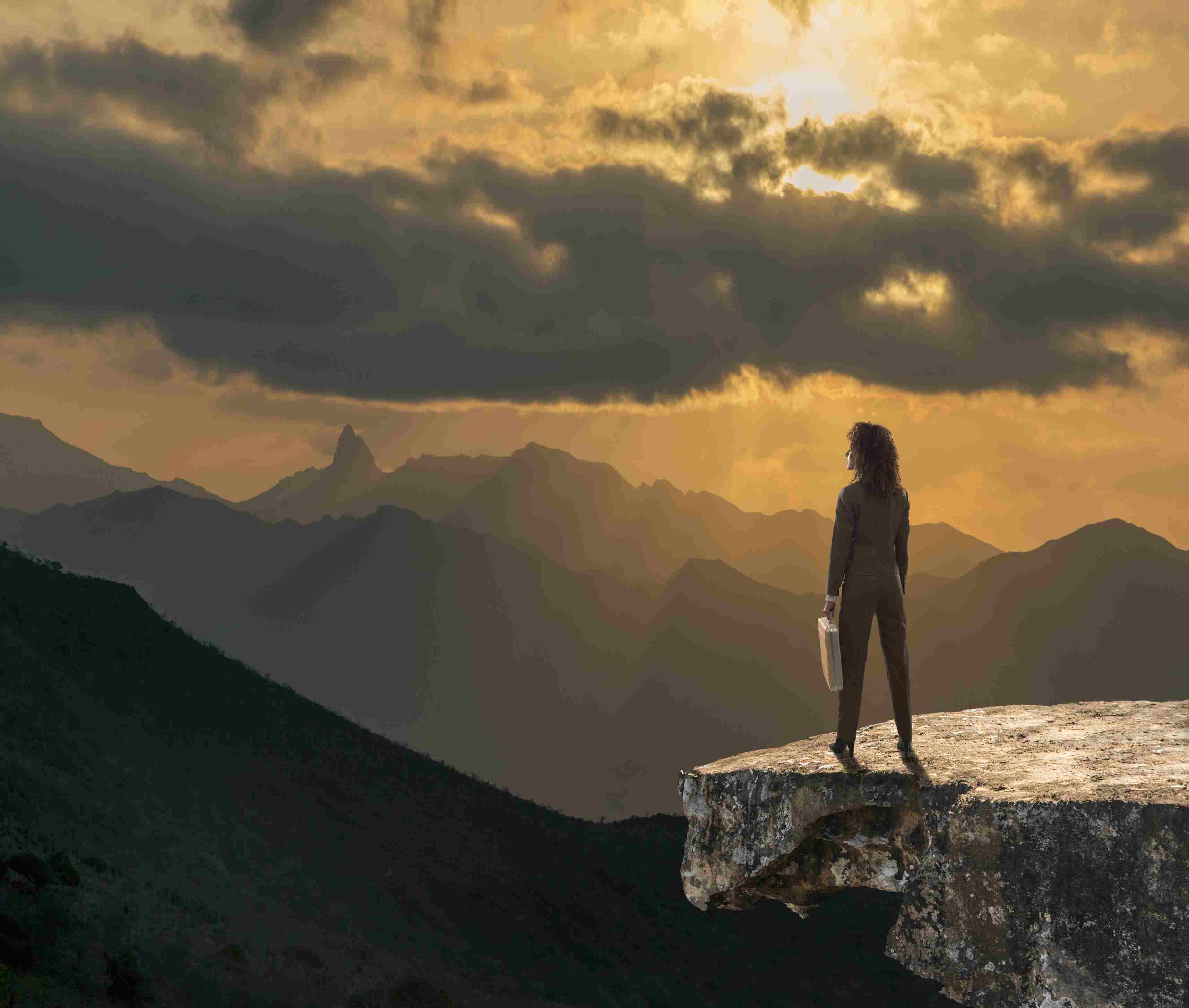A woman with a briefcase on top of a mountain