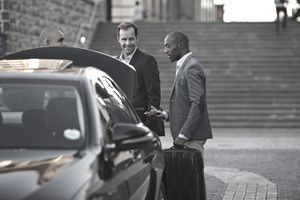 Driver assisting businesspeople with luggage at taxi station