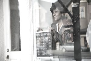 Small business owner placing a store hours sign in the shop window.