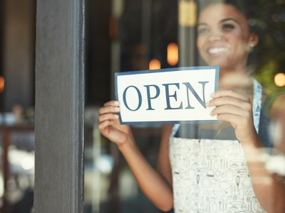 Woman hanging an open sign in the window of a cafe.