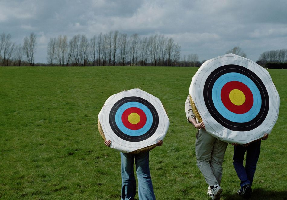 Three archers carrying targets on backs, outdoors, rear view