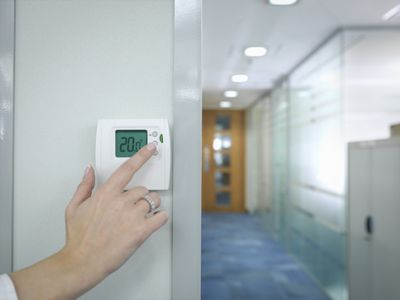 Close up of office worker adjusting thermostat