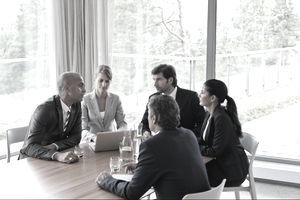 Male and female businesspersons gathered around a conference table