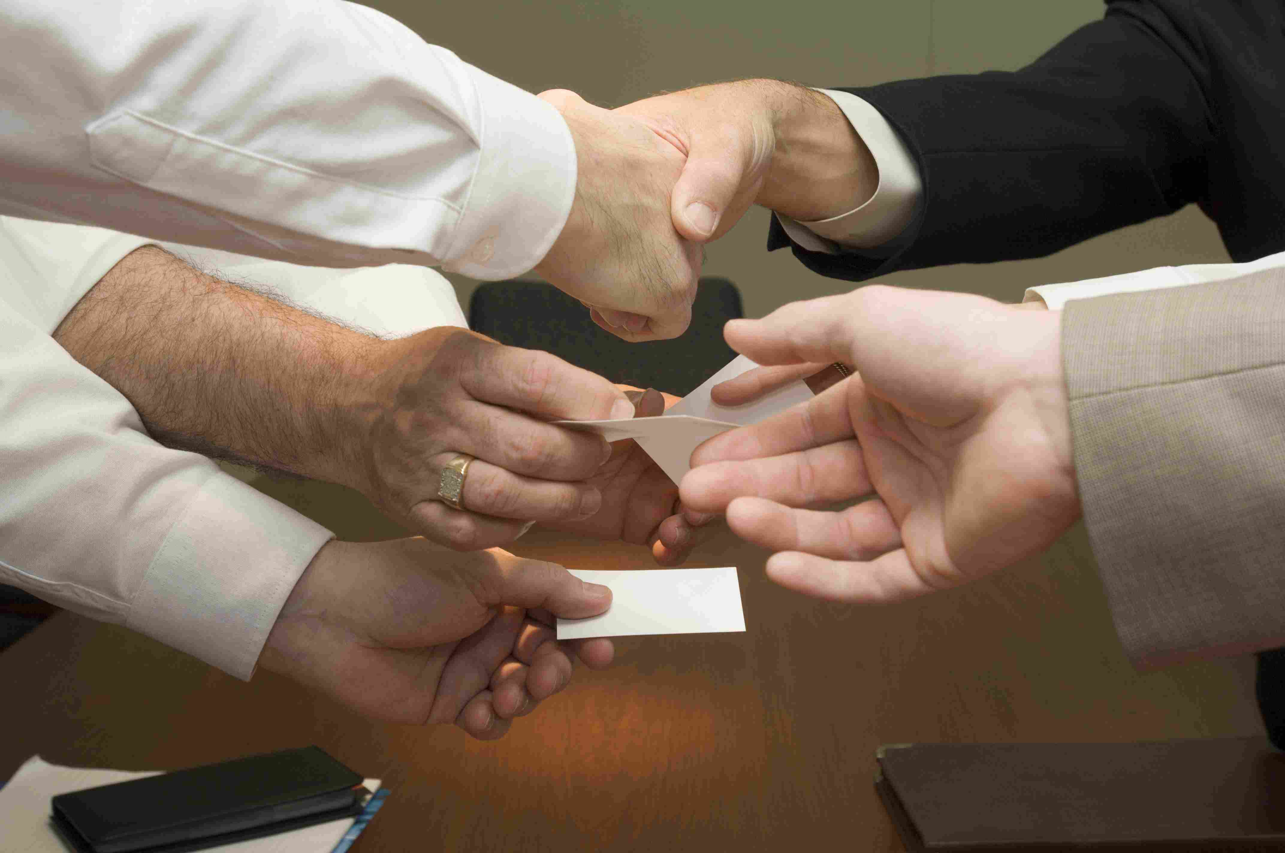 Multiple hands exchanging business information