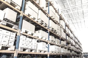 Warehouse designed with rows of shelves full of boxes stacked on pallets.