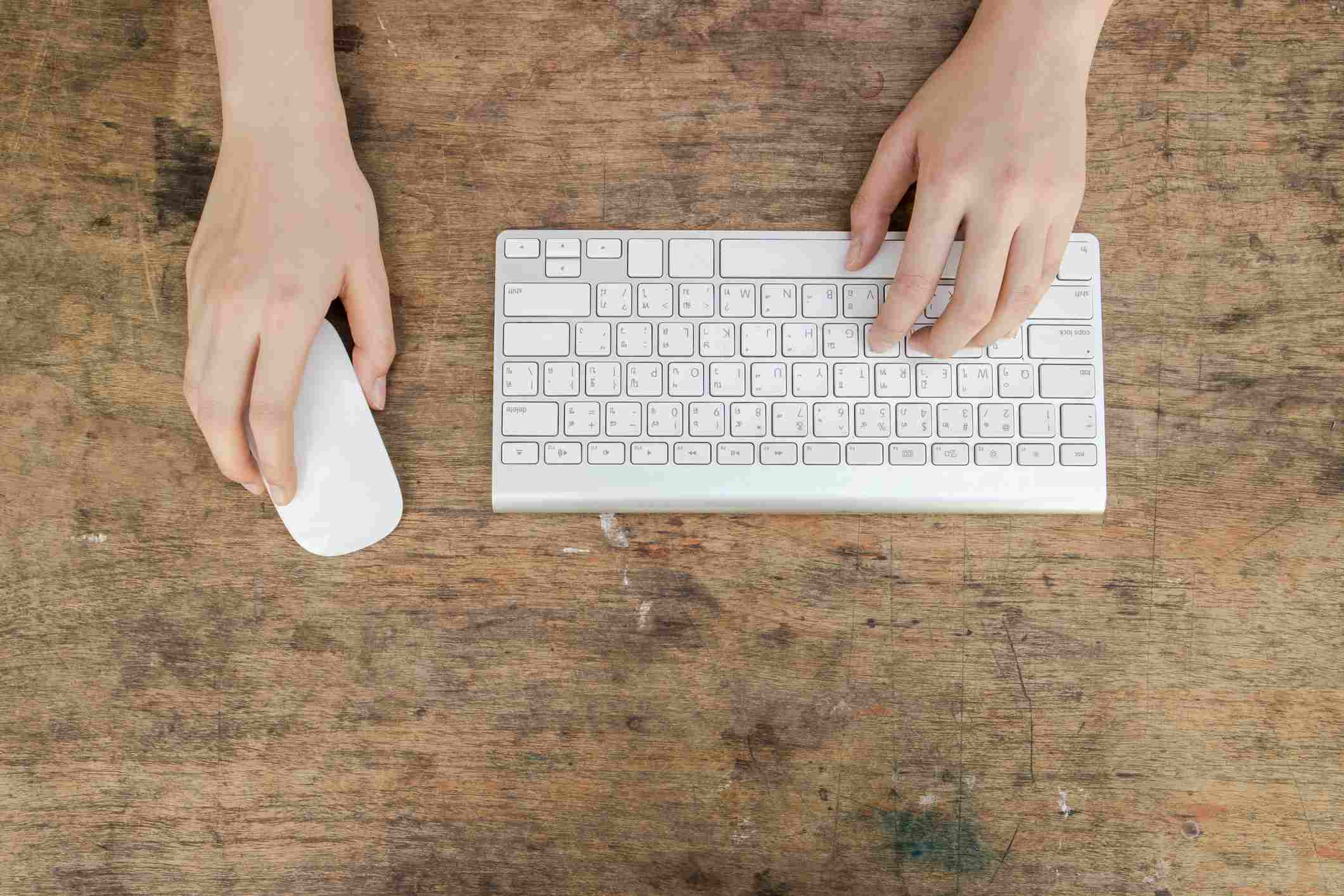 Directly Above Shot Of Person Using Computer Keyboard With Mouse