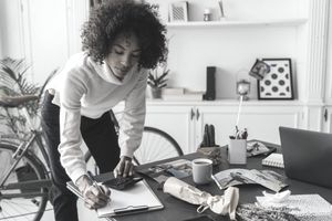 A woman entrepreneur leans over a crowded desk and checks figures from a calculator and writes them onto a clipboard.