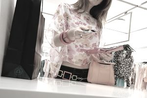 Young woman holding credit card at counter in clothes shop