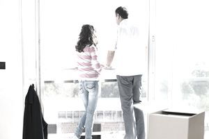 young couple looking over balcony in a Florida rental apartment with packing boxes behind them