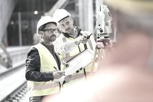 Two construction workers looking at blueprints on a construction site.
