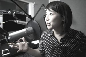 Young woman speaking into a professional microphone in a booth for a podcast.