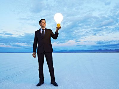 Man standing in empty expanse holding a lightbulb indicating he has an idea