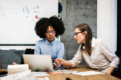 Two young women having a discussion in a business