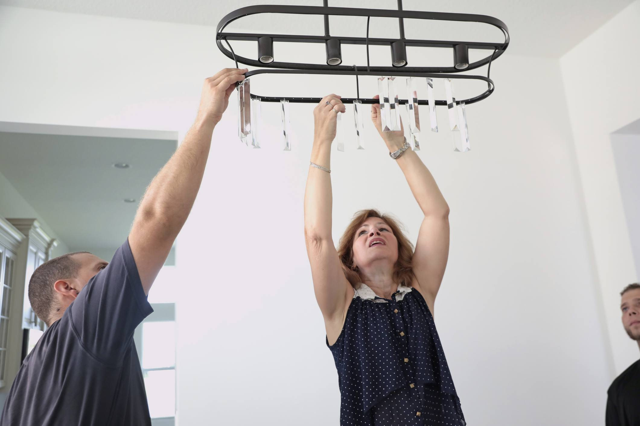 Professional home staging consultant helping install a chandelier in home for sale