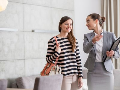 Female estate agent showing mid adult woman around property