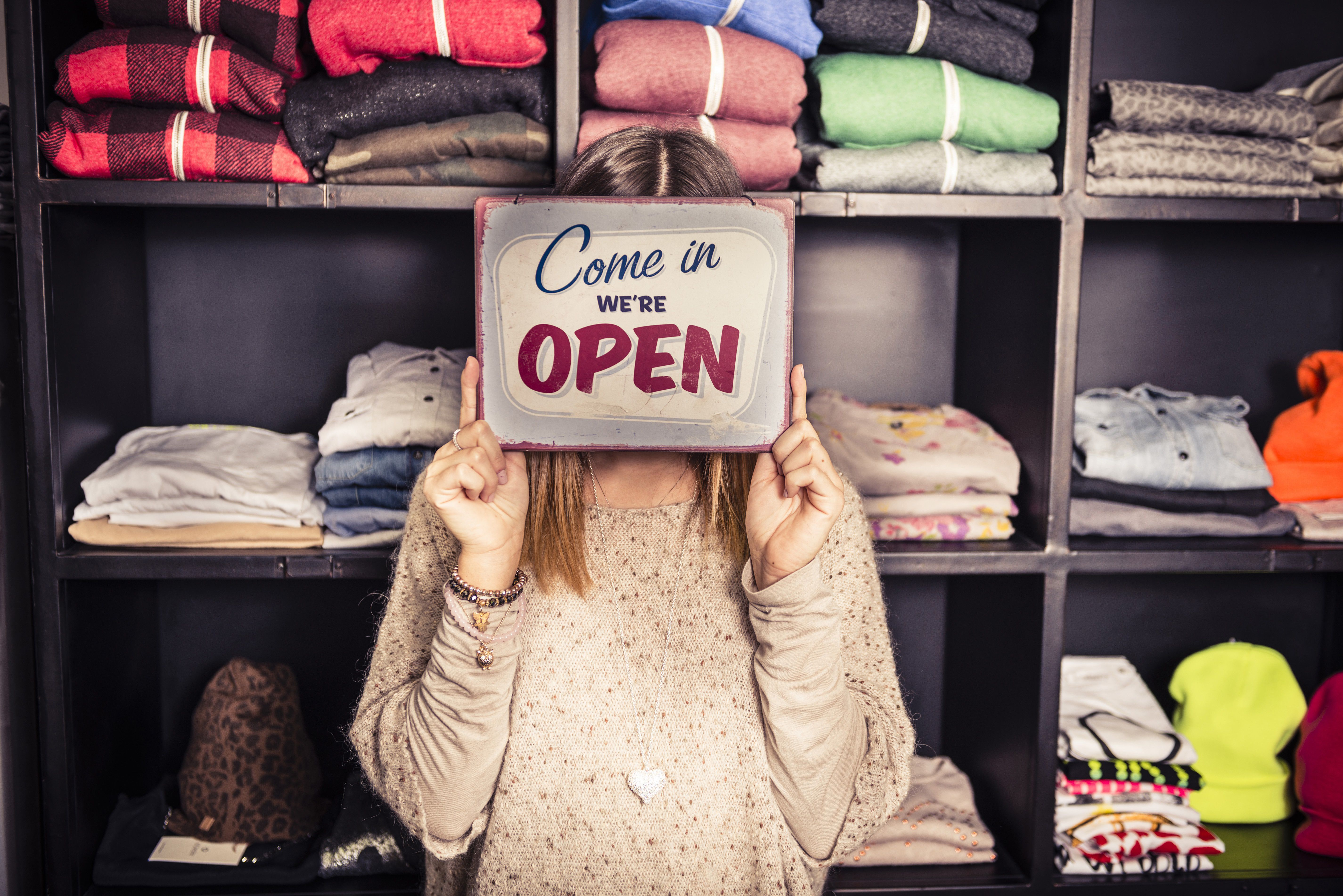 """Businessowner in front of a display of folded shirts holding up a """"Come in we're open"""" sign."""