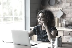 Pensive African American woman work on laptop thinking