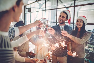 Employees in Santa hats with champagne ad sparklers