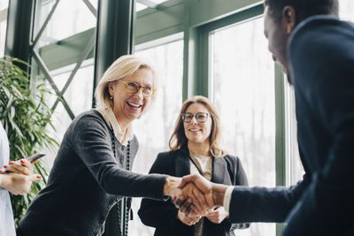 Senior businesswoman greeting colleagues during conference