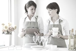 Two female caterers with dishware