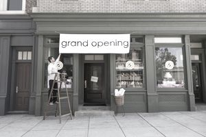 Business owner putting up grand opening sign