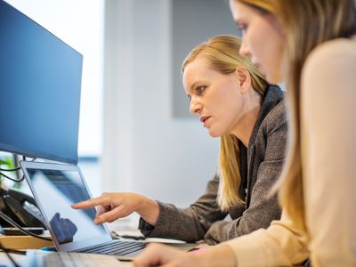 Two women designing a direct mail package on a computer.
