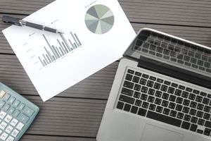 Computer and graph on a table, calculating the ROI ratio of an investment.