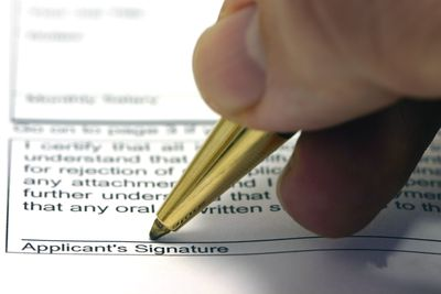 Close up of a hand signing a small business grant application