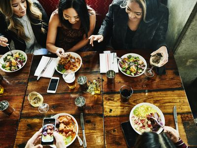 Overhead view of friends sharing lunch in a restaurant sitting at a large wood table..