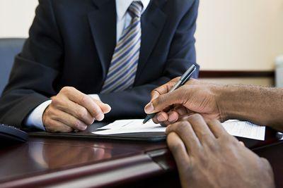 Customer signing paperwork to open a business account with a bank manager.