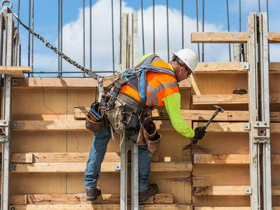 Caucasian worker hammering wood at construction site