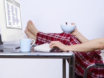 Working at home in pajamas with feet up on the desk