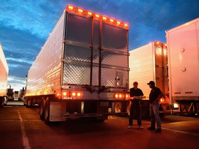 Two commercial OTR drivers standing by a semi truck trailer at a truck stop.