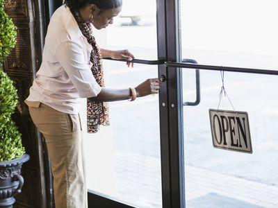 Business owning locking front door of business sign saying open