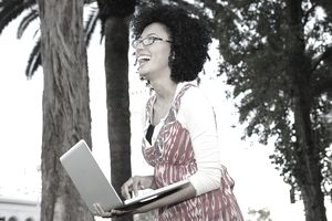 Woman using laptop in outdoor setting.