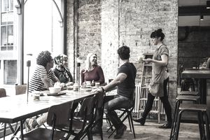 Group of friends being served in a coffee shop